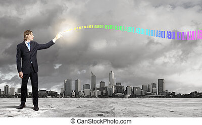 Businessman with colourful light beam in his hands -...