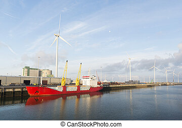 red cargo boat in harbor with wind mills for energy