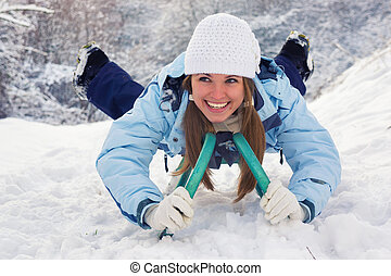 lying on a sled 2 - Young adult woman lying on a sledge and...