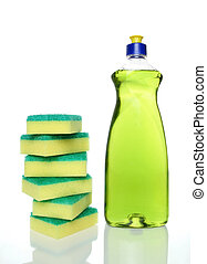Bottle of green dishwashing liquid and sponges on white...