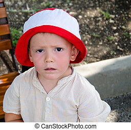 Sad little boy with a woebegone expression standing in a red...