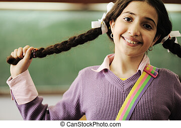Cute little girl with hair braids at school