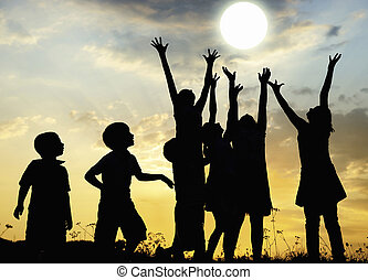Children rising arms to sun on meadow