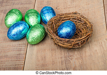 Small bird's nest with green and blue foil eggs