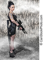 Woman with Assault Rifle - Beautiful young woman holding an...