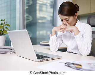 asian businesswoman sitting and thinking in office, looking...
