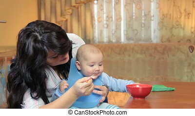 Mother feeding her baby boy with a spoon at home
