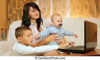 Mother with children using laptop at home
