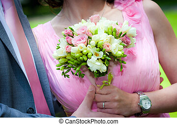Young married couple holding hands with wedding bouquet
