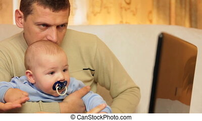 Father and baby using laptop at home