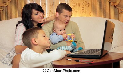 Family using laptop at home - Happy family in living room...
