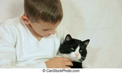 Child stroking cat at home