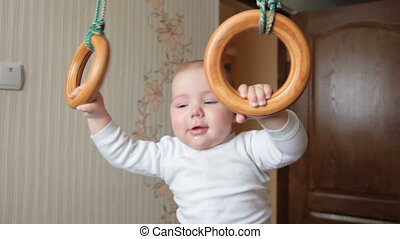 Kid on gymnastic rings - 7 months baby boy hanging on...