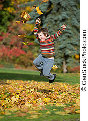 boy playing in fall leaves - boy jumping in pile of leaves