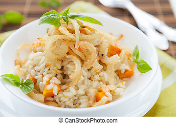 risotto with crispy onions in whie bowl, closeup