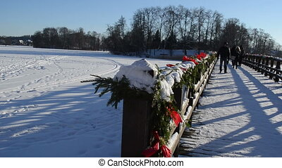 bridge winter people - wooden lake bridge with christmas...