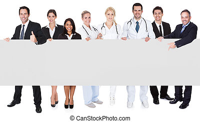 Doctors and managers presenting empty banner - Group of...