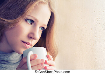 beautiful dreamy girl with a cup of hot coffee at the window...