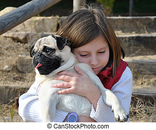 girl with her pug dog - picture taken in the street of a...