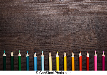 multicolored pencils over brown wooden table background -...