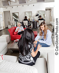 Woman Having Manicure With Customers Waiting At Parlor - Mid...