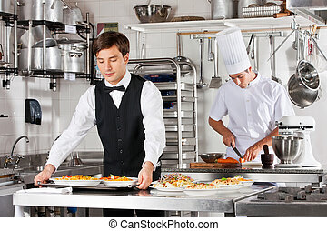 Waiter And Chef Working In Kitchen - Young waiter carrying...