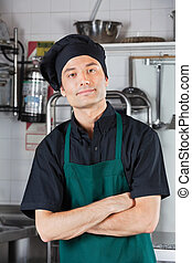 Male Chef With Arms Crossed In Kitchen - Portrait of...