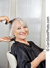 Senior Woman Getting Hair Styled In Salon - Portrait of...
