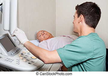 Patient Looking At Ultrasound Machines Screen - Young male...