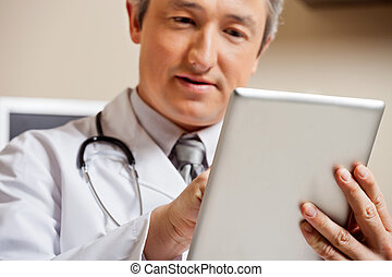 Doctor Using Digital Tablet - Close up of mature male doctor...