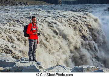 Man standing near Dettifoss waterfall