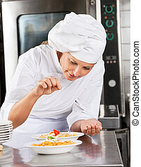 Chef Adding Spices To Dish - Female chef adding spices to...