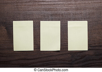 three blank stickers on brown wooden table - three blank...