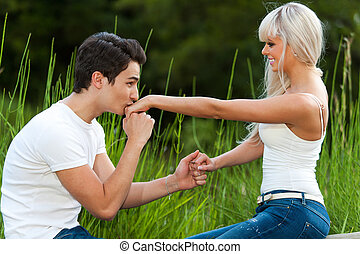 Boyfriend kissing girls hand outdoors. - Portrait of young...