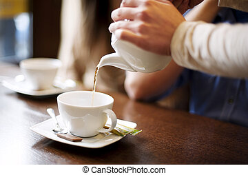 Waitress pouring cup of coffeetea