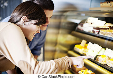 Young woman pointing on cakes in confectionery