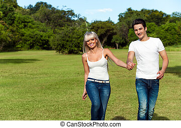 Young couple hopping together in park.