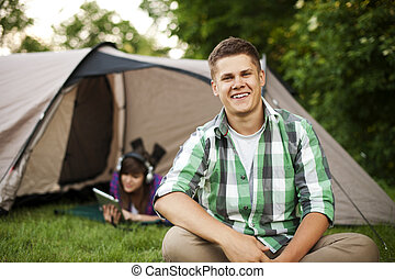 Young man sitting in front of tent