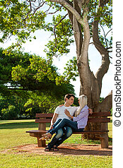 Young couple sitting on bench in park.