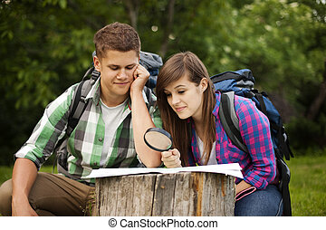 Young couple with map in forest