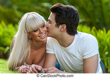 Young man kissing girlfriend on cheek - Close up portrait of...