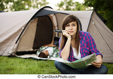 Beautiful young woman sitting in front of tent