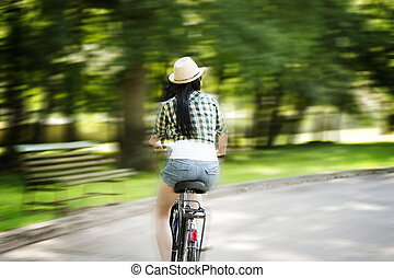 Young woman cycling through the park