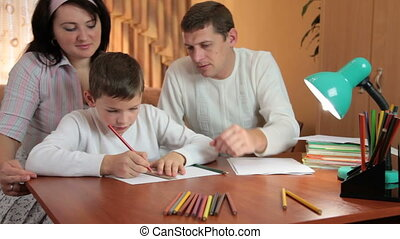 Family doing homework at home - Father and mother helping...