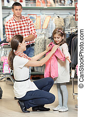 woman and little girl shopping clothes - woman and little...