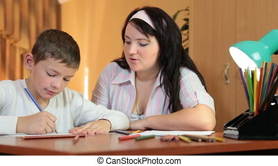Mother and son doing homework at home