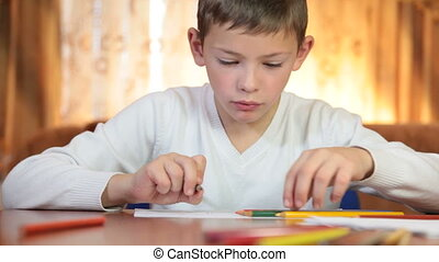 Child doing homework at home - 9 year old boy doing homework...