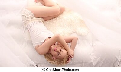Model in white bed, seen from above - Blonde girl wearing...