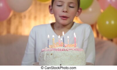 Kid blowing out candles - child celebrating his birthday...
