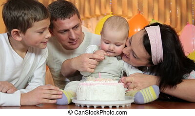 Family with birthday cake - Young family celebrates the...
